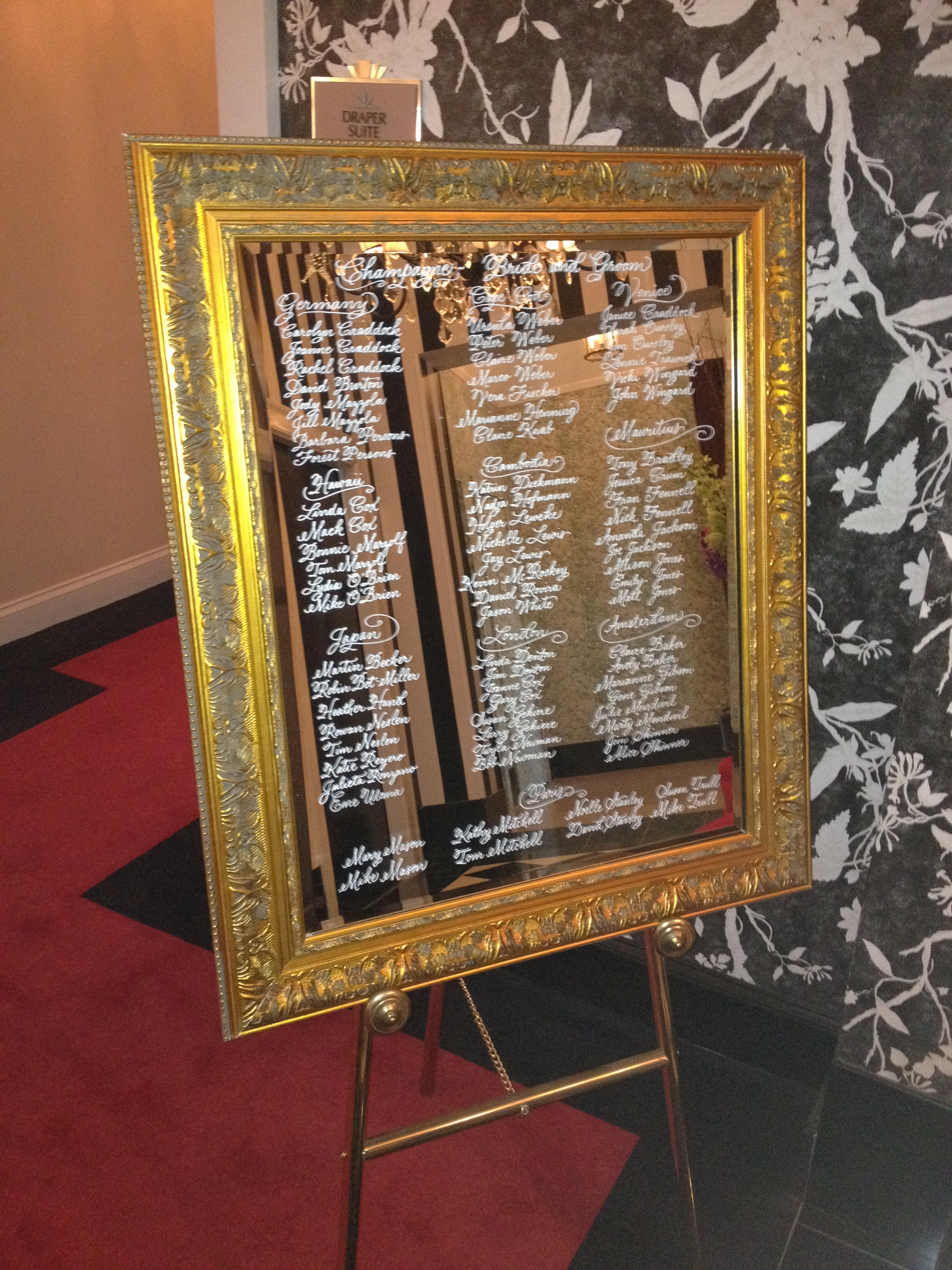 Table seating chart hand lettered on mirror at wedding venue